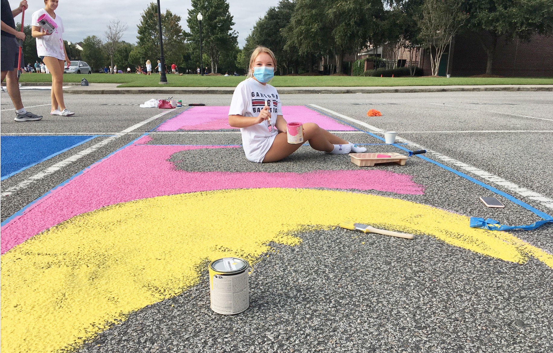 Mary Parker McLaughlin, 17, proudly displays her pink and yellow colored parking spot. When she's finished painting, she said it will resemble a smiley face design.