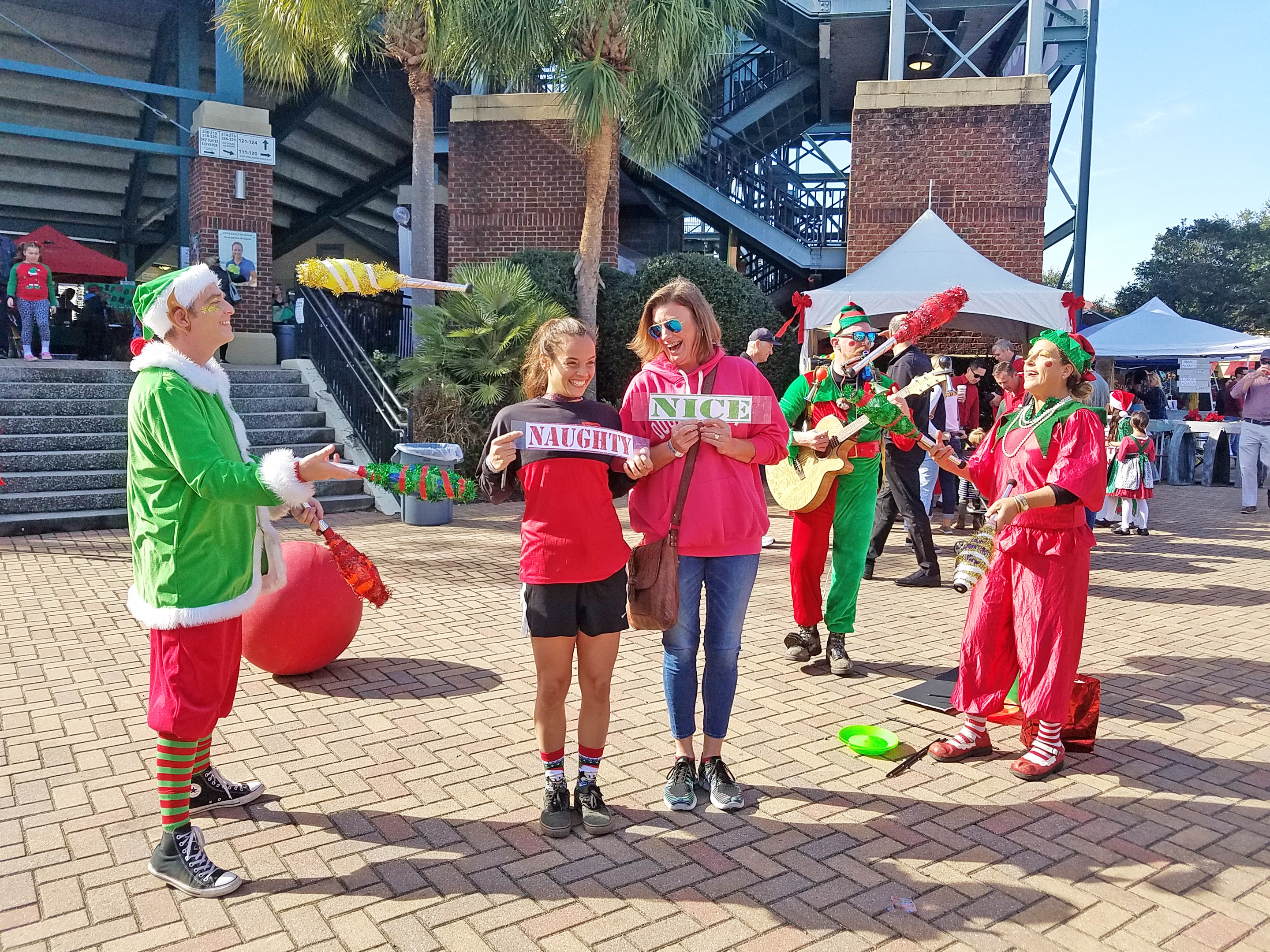 """Rachel Wasilak and Tara Meyer were happy volunteers for Good Clean Fun's juggling act. There was some debate as to whether the """"Naughty"""" and """"Nice"""" signs got mixed up!"""