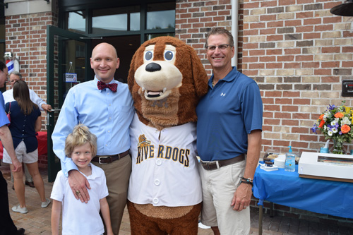 Owners Glenn Raus, Michael Cole and Cole's son pose with Charlie, the Charleston Riverdog's mascot.