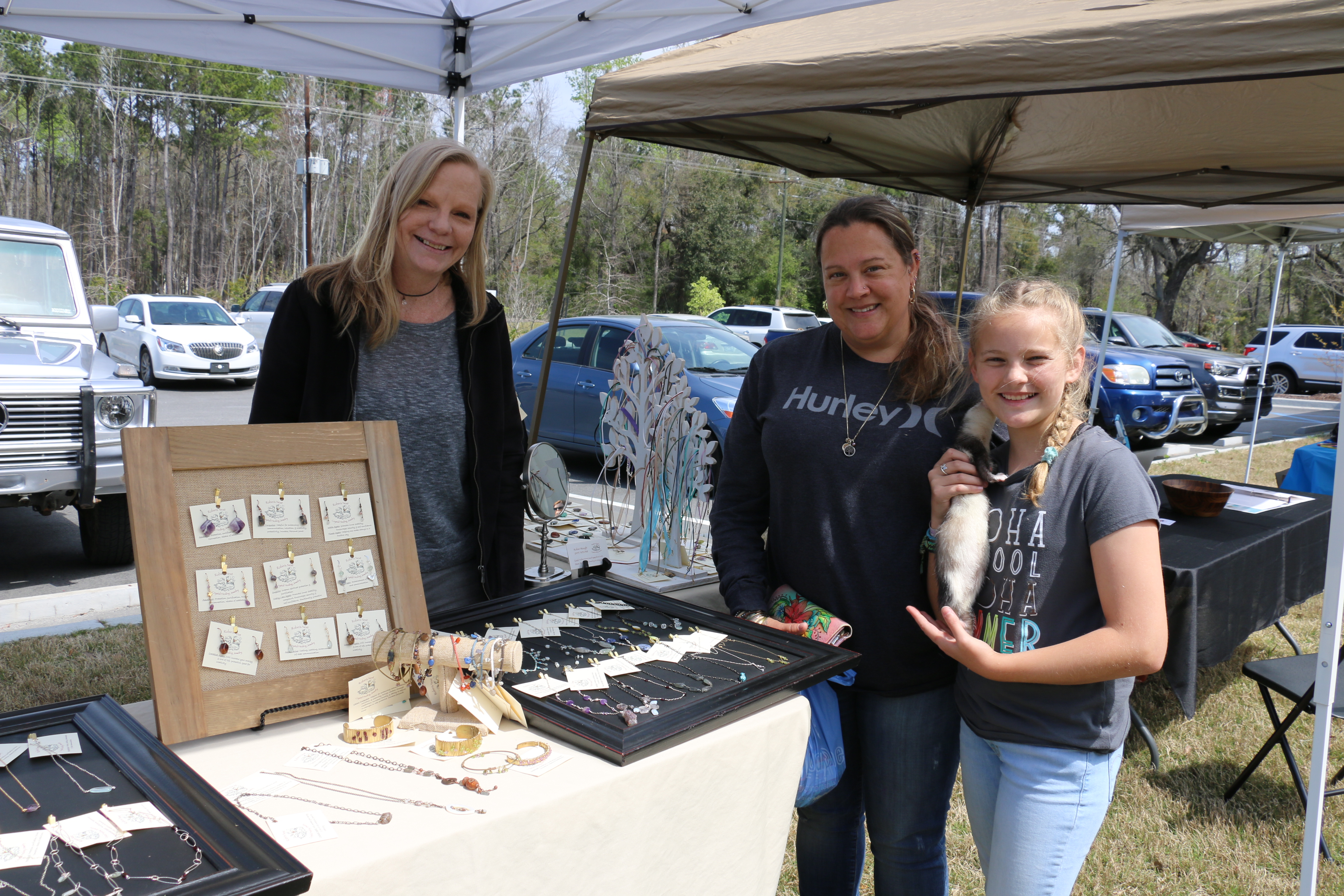 Mary and Mea Arthur, and their ferret Kira, browse at Robin's Next Crystal Healing Jewelry with owner Robin Waugh.