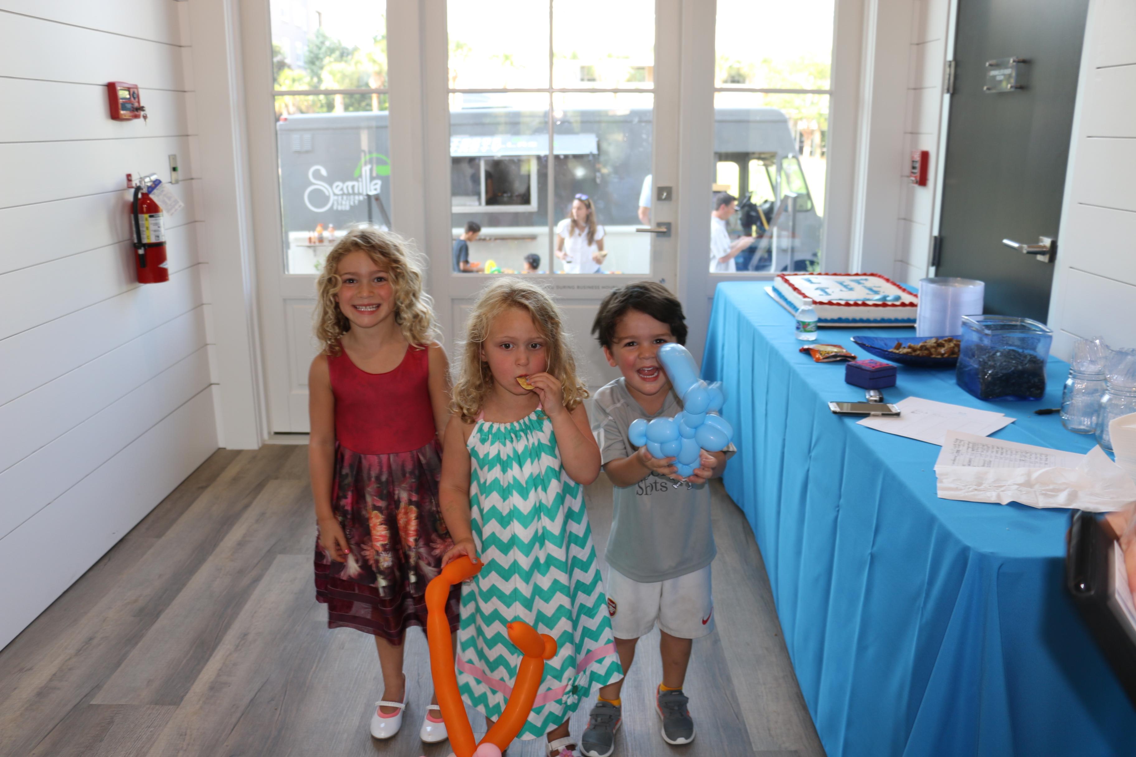 Maddie Zechmann, Kate Zechmann, and friend Grant Williams anxiously wait for the cake cutting.