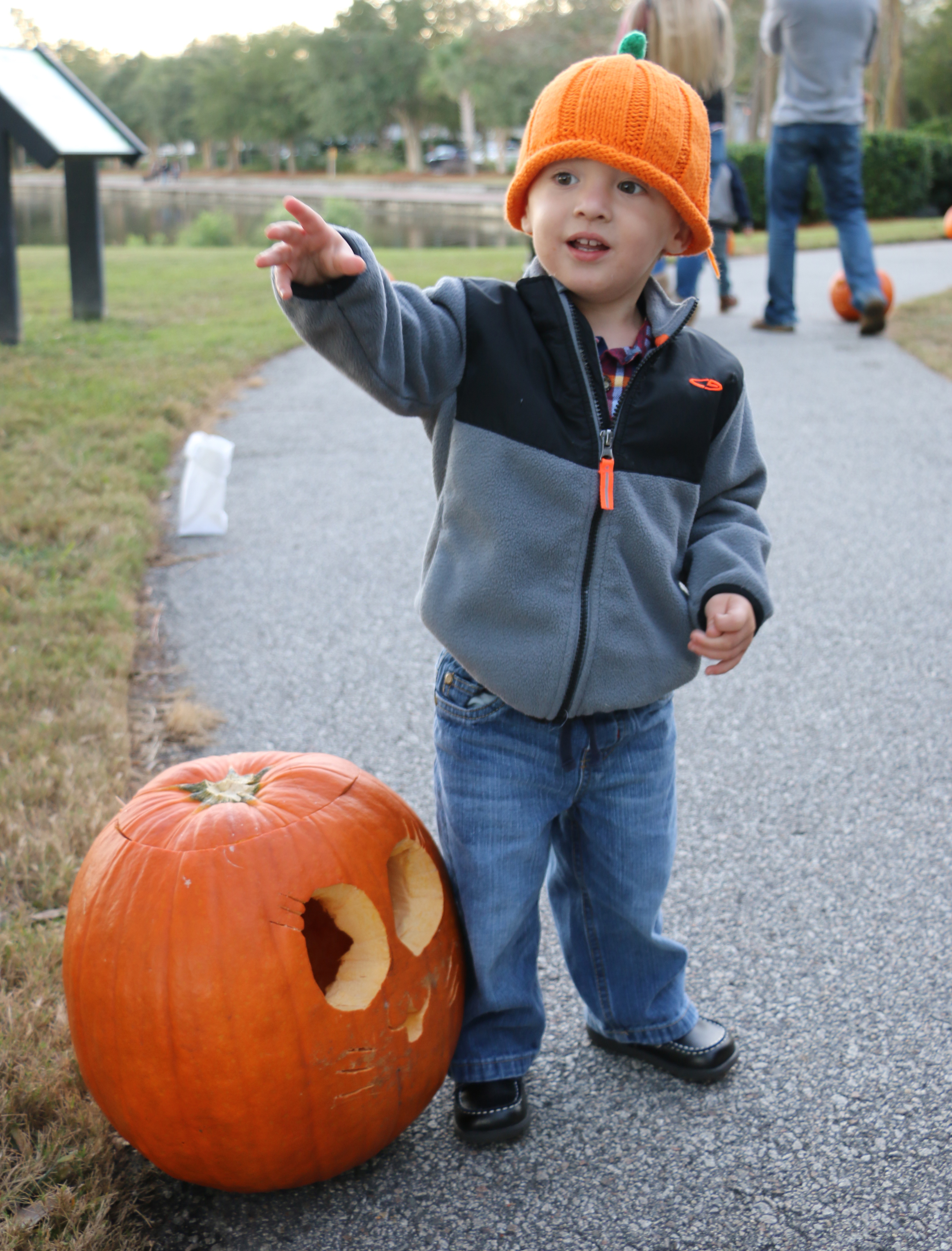 A cute lil' pumpkin! Theodore poses next to one of the many jack-o-lanterns along the path at Smythe Park.