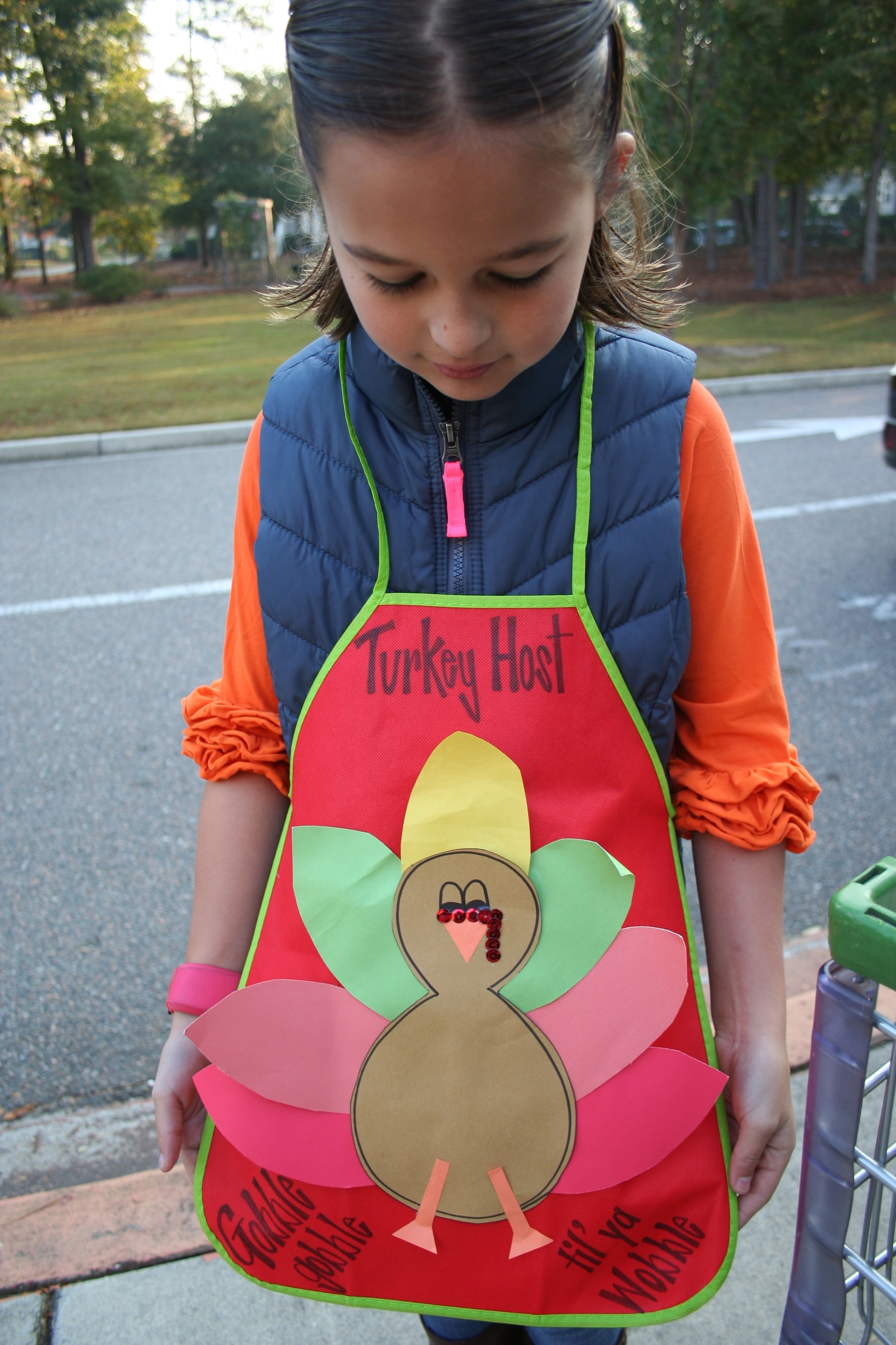 "Emma Ladd proudly displays her ""Turkey Host"" apron."