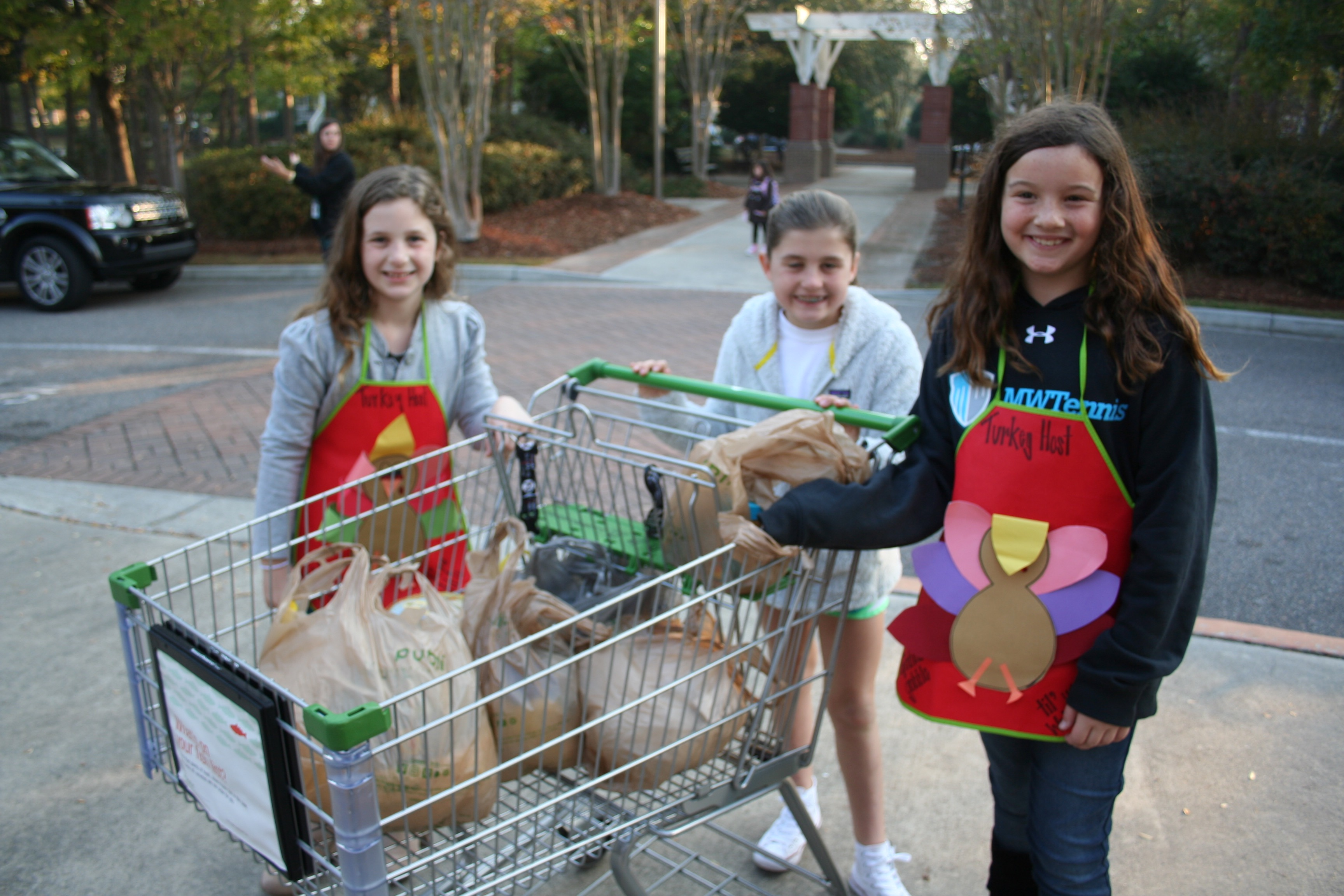 Birds of a feather flock together - Amelia Perkis, Emma Roberts, and Abby Shivley happily greet morning carpool riders during the school's recent Frozen Turkey Drive