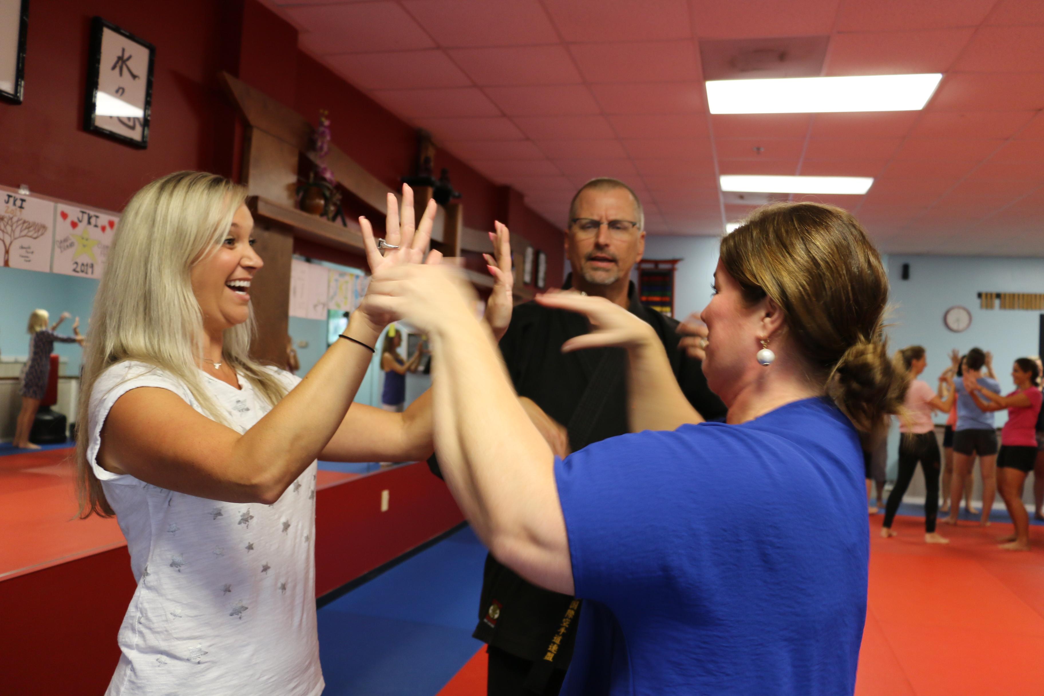 "Sensei Glenn of Japan Karate Institute instructs Caroline Lane and Virginia DiMascio on the ""finger flick"" technique."