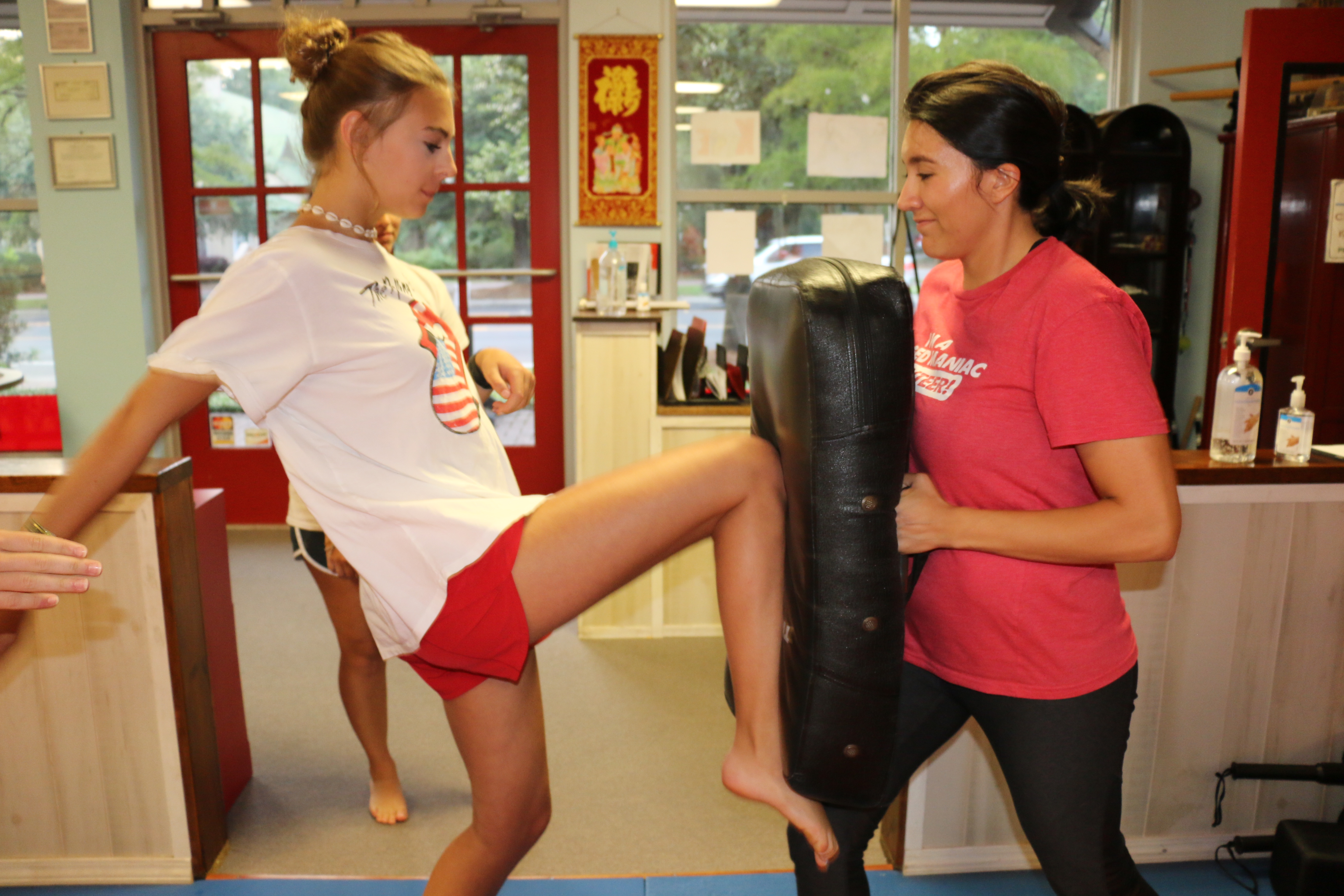 """Juanita Bustamante holds the pad as Alejandra Gomez practices the """"knee to groin"""" defense technique."""