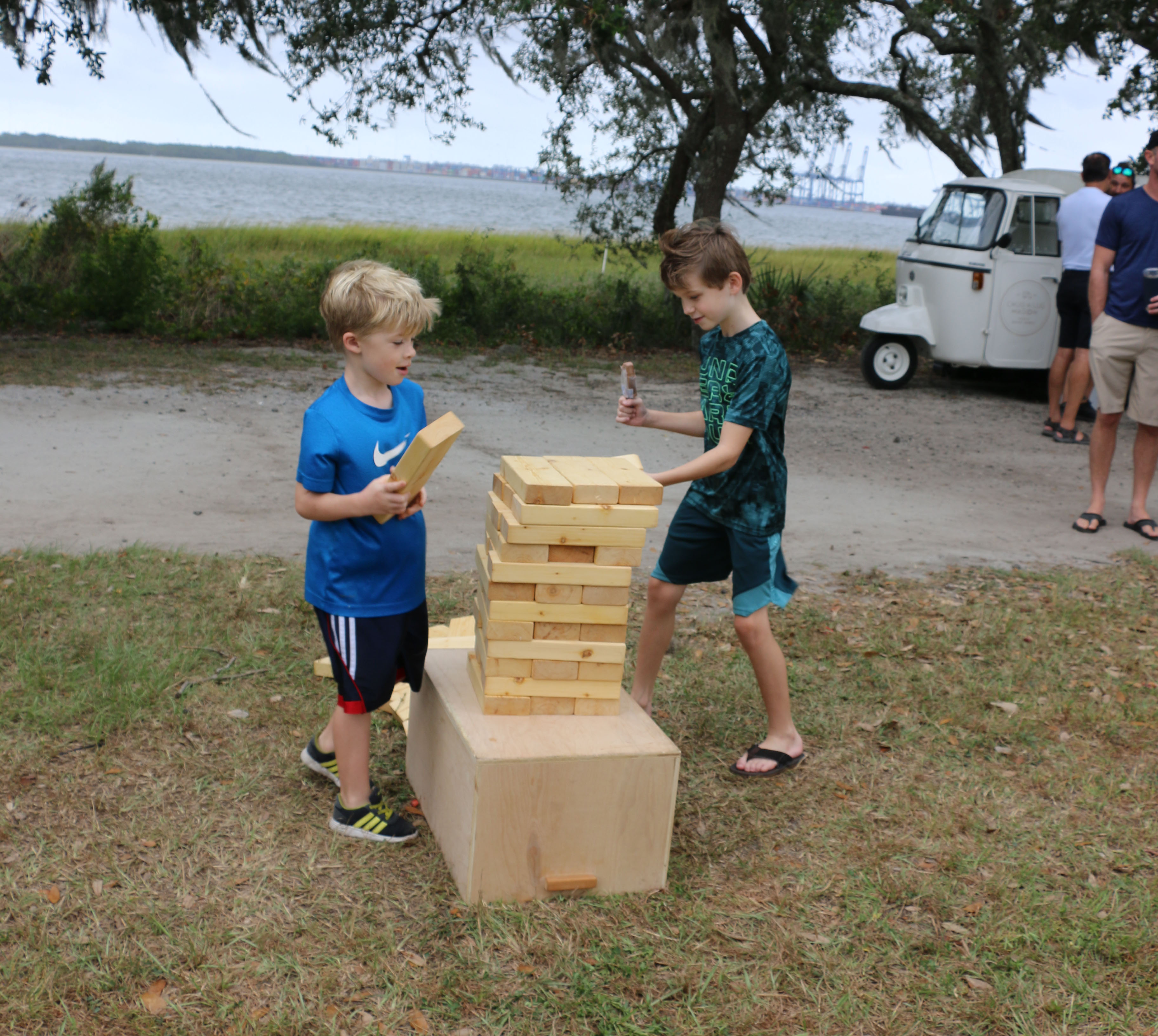 Boys have fun building and playing with a giant Jenga set.