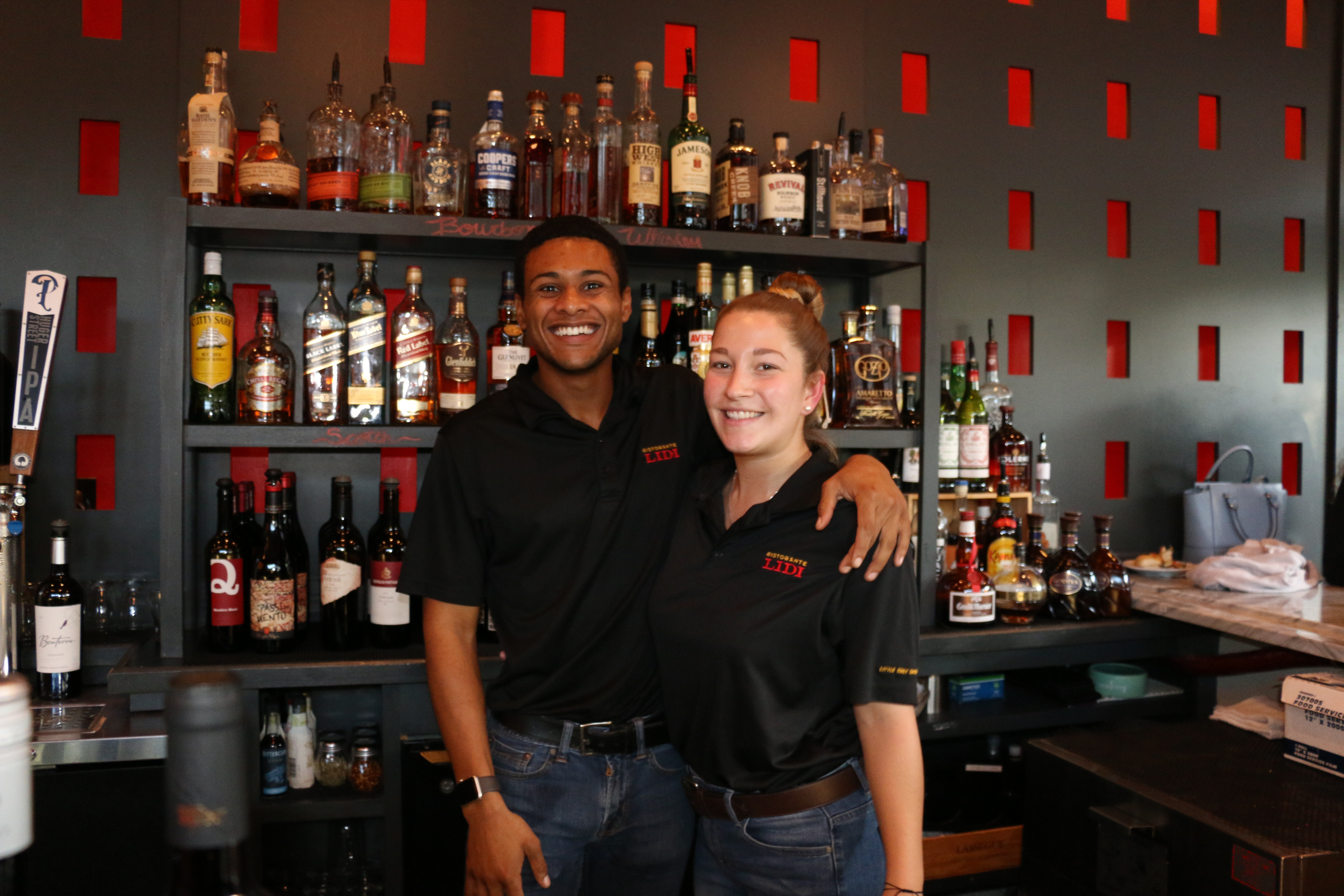 LIDI bartenders Quentin Scrivens and Laura Antonelli serve drinks with a smile.