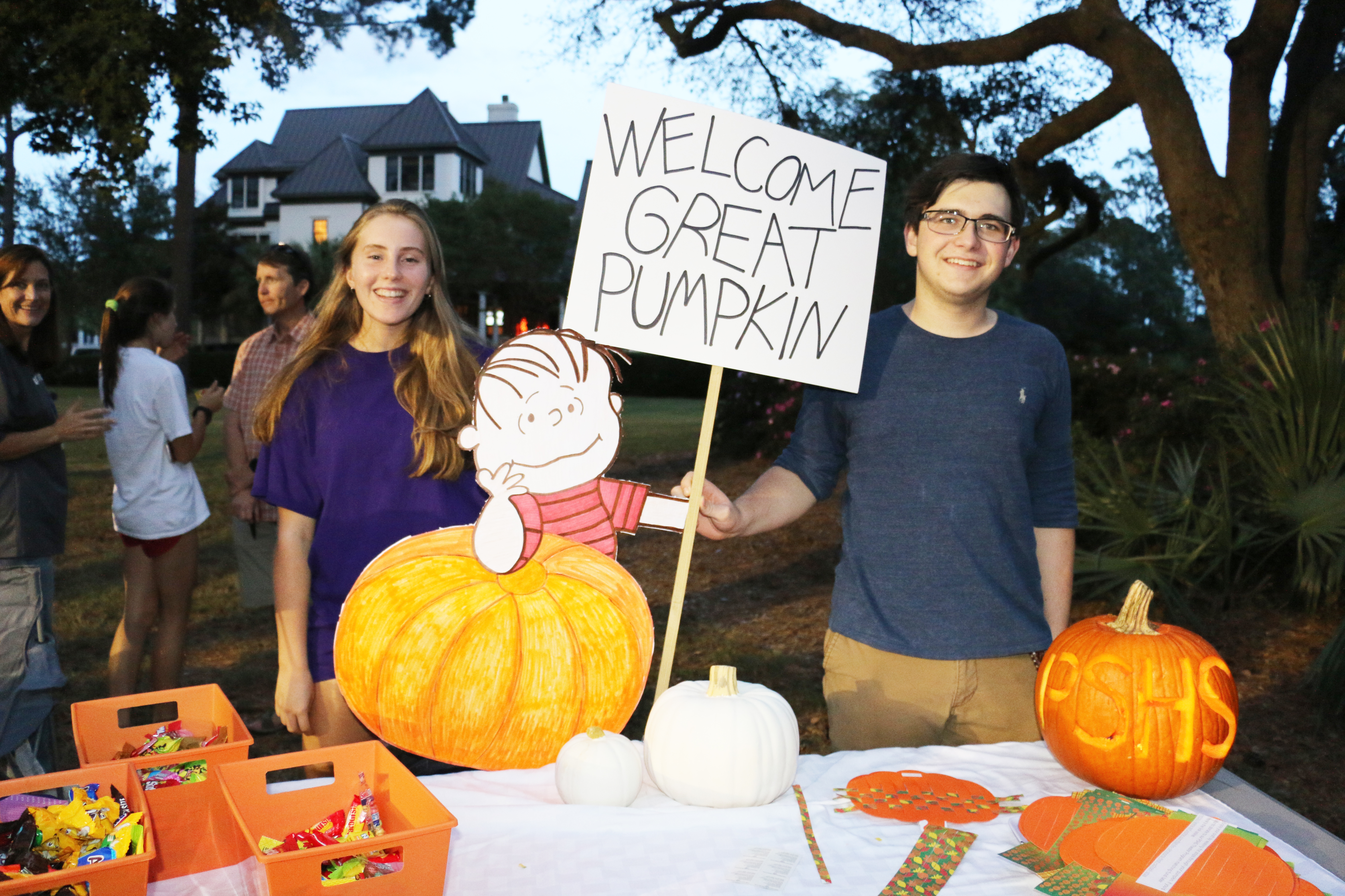 Camille Fei and Emmett Gately welcome guests to the Philip Simmons High School table with their Great Pumpkin sign.