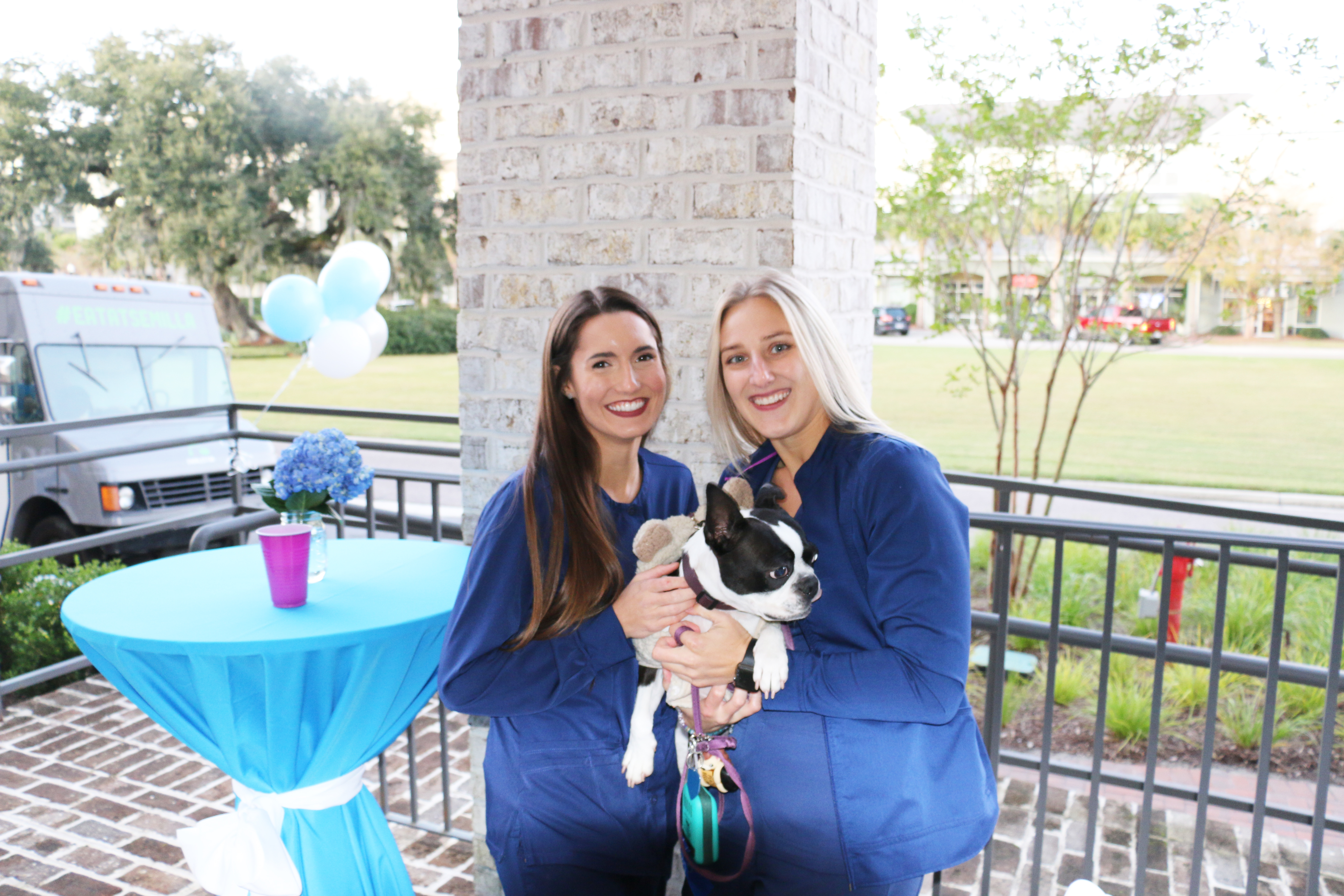 Morgan and Candis, dental hygienists, stay warm during the cool evening celebration by snuggling with their furry friend, Jazz.
