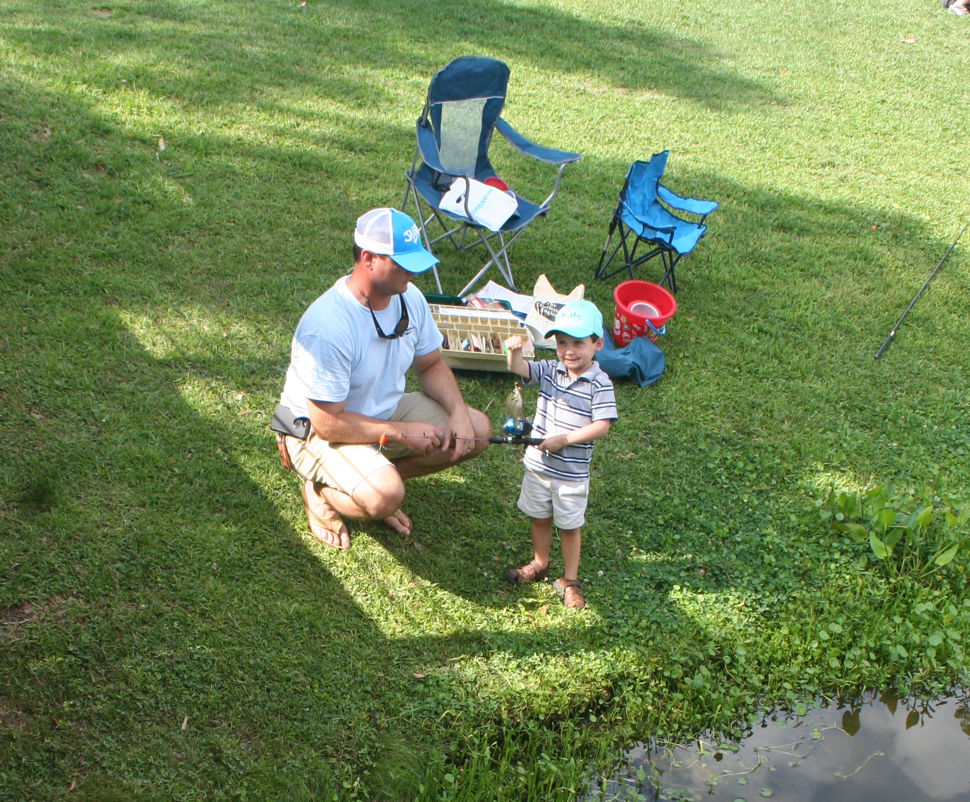 Whit Ford reels in a fish! His dad, Ryan, helps with the release.