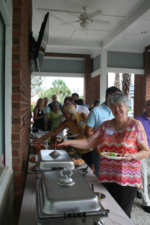 Long time Daniel Island resident Kay Uhler serves herself some the great food provided by Refuel at last week's DIBA happy hour.