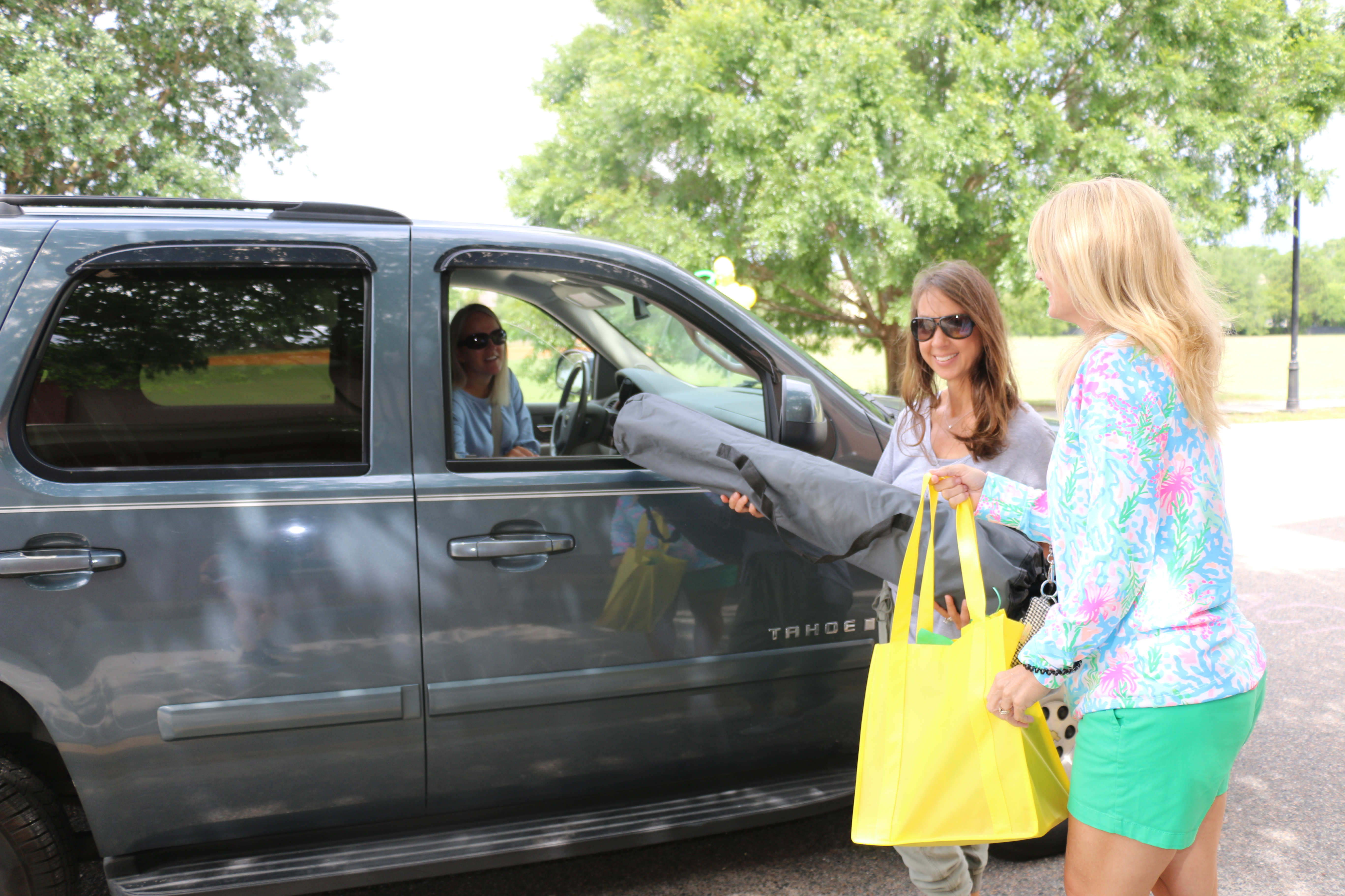 Kindergarten assistant Tyler Love, in her car, receives a bunch of goodies from Principal Nancy Leigh (in pink) and office assistant Denise Ketterman.