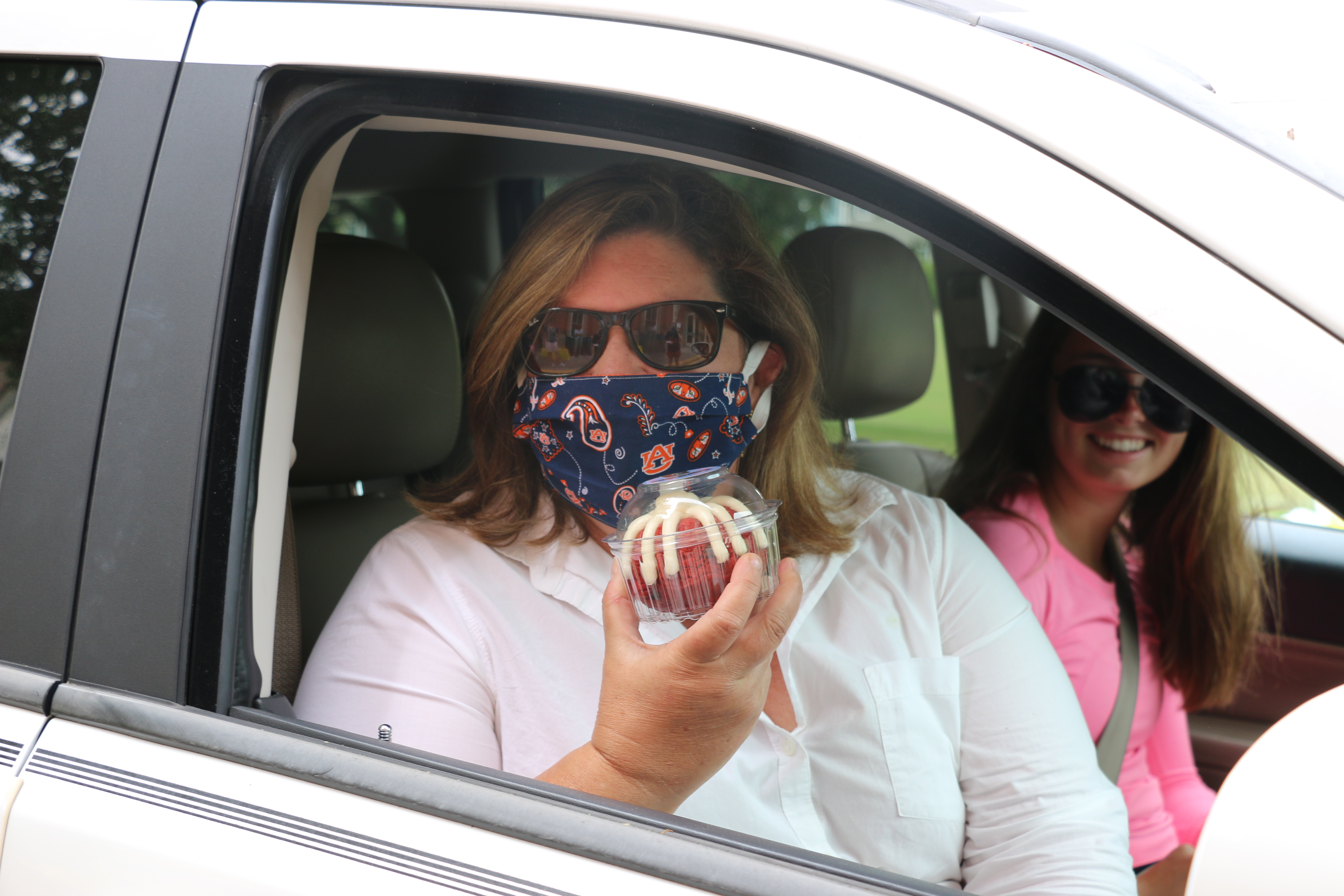 Kindergarten teacher Kelly Cobb, wearing a mask and holding a treat, was escorted to the teacher appreciation event at Daniel Island School by her daughter, Amelia.