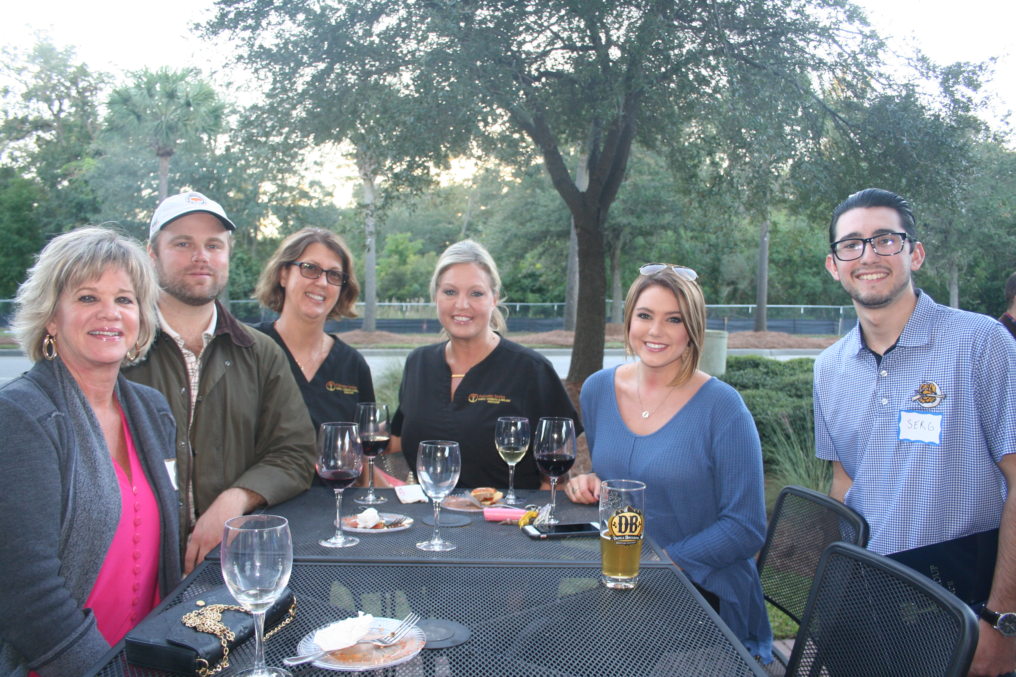 Rick Dolin, Andrew Thomas, Nancy Demott, Perri Fry, Caroline Thomas and Serg Saradjian share food, drink and fun at a LIDI outside table during the Daniel Island Business Association Block Party on Oct. 26.