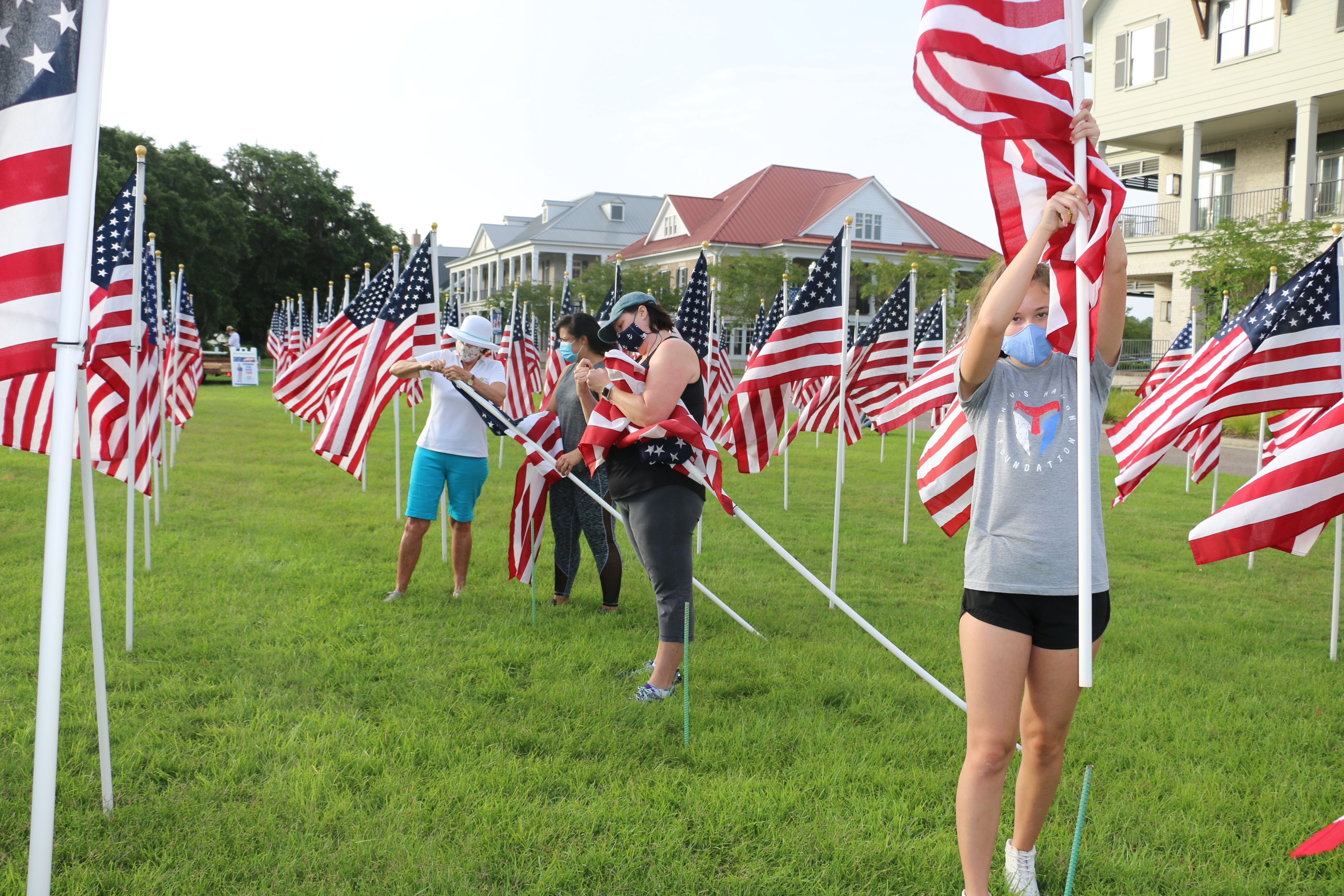 Sandy Dominick, Severa Padilla, Beckie Davey and Emily Davey unfurl and place American Flags at the Field of Honor last weekend.