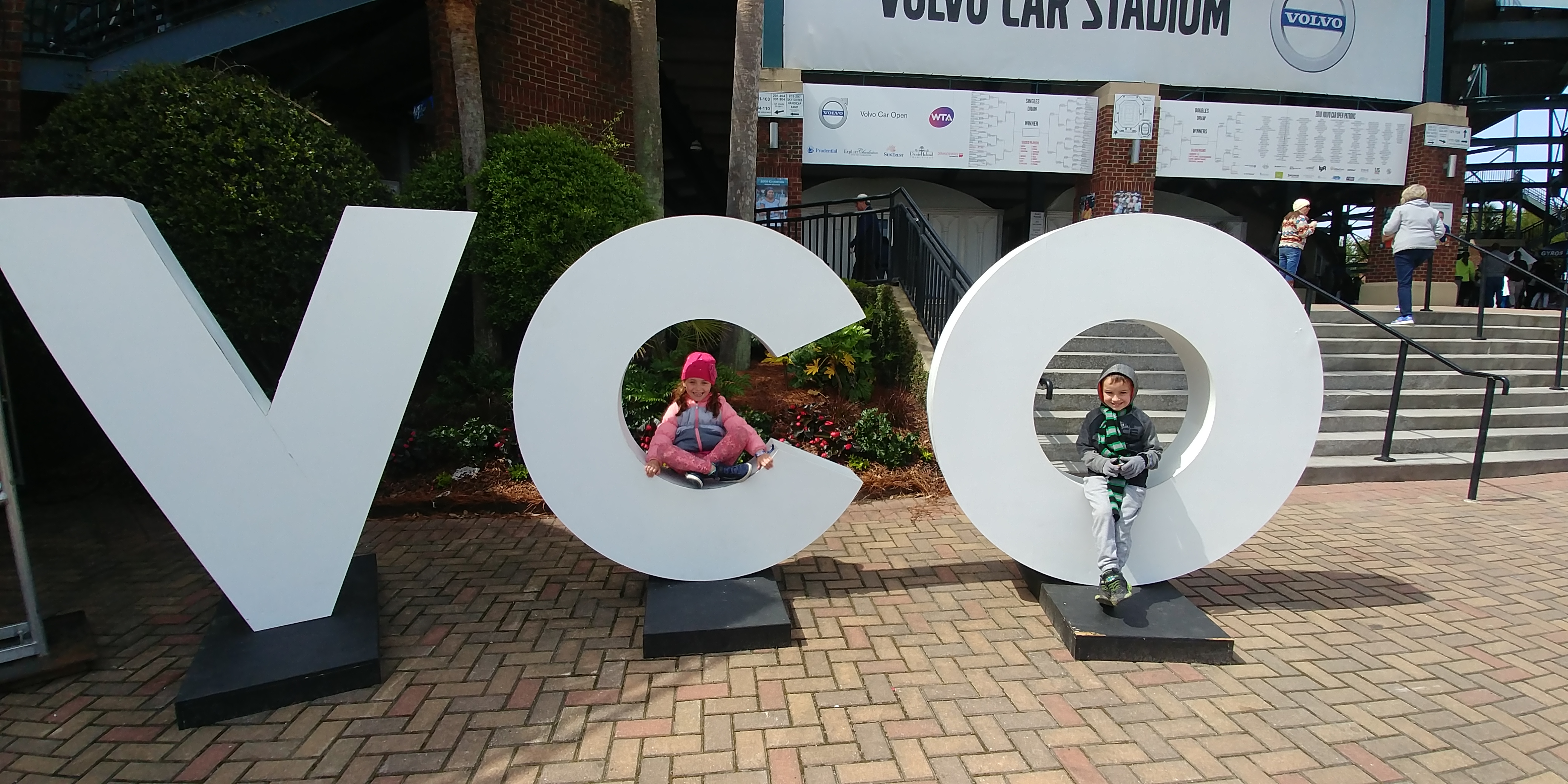 Lily Rae and Torin pose in two of the Volvo Car Open initials.