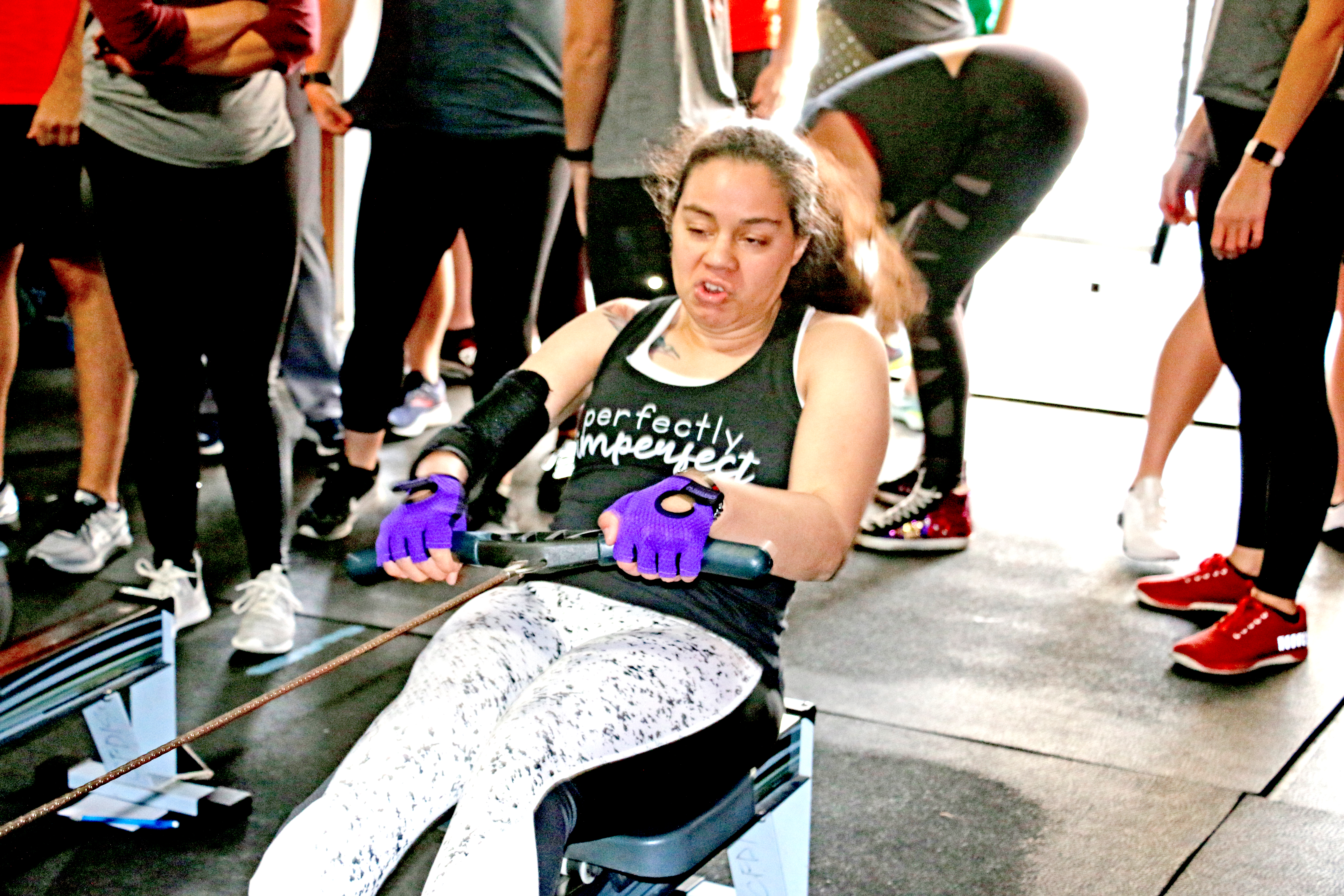 "Sullivan Ikemoto, a Special Olympian competing in the ThROWdown, displays the ""perfect"" attitude, both on her shirt and with her rowing effort!"
