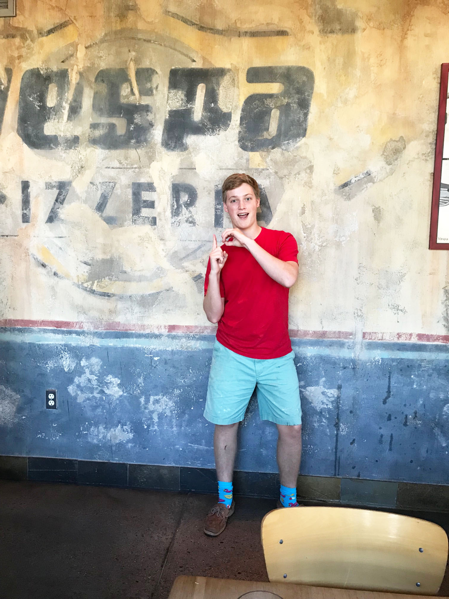 """Vespa employee John Kraft holds up a big """"1 - 0"""" in honor of the eatery's 10 years on Daniel Island."""
