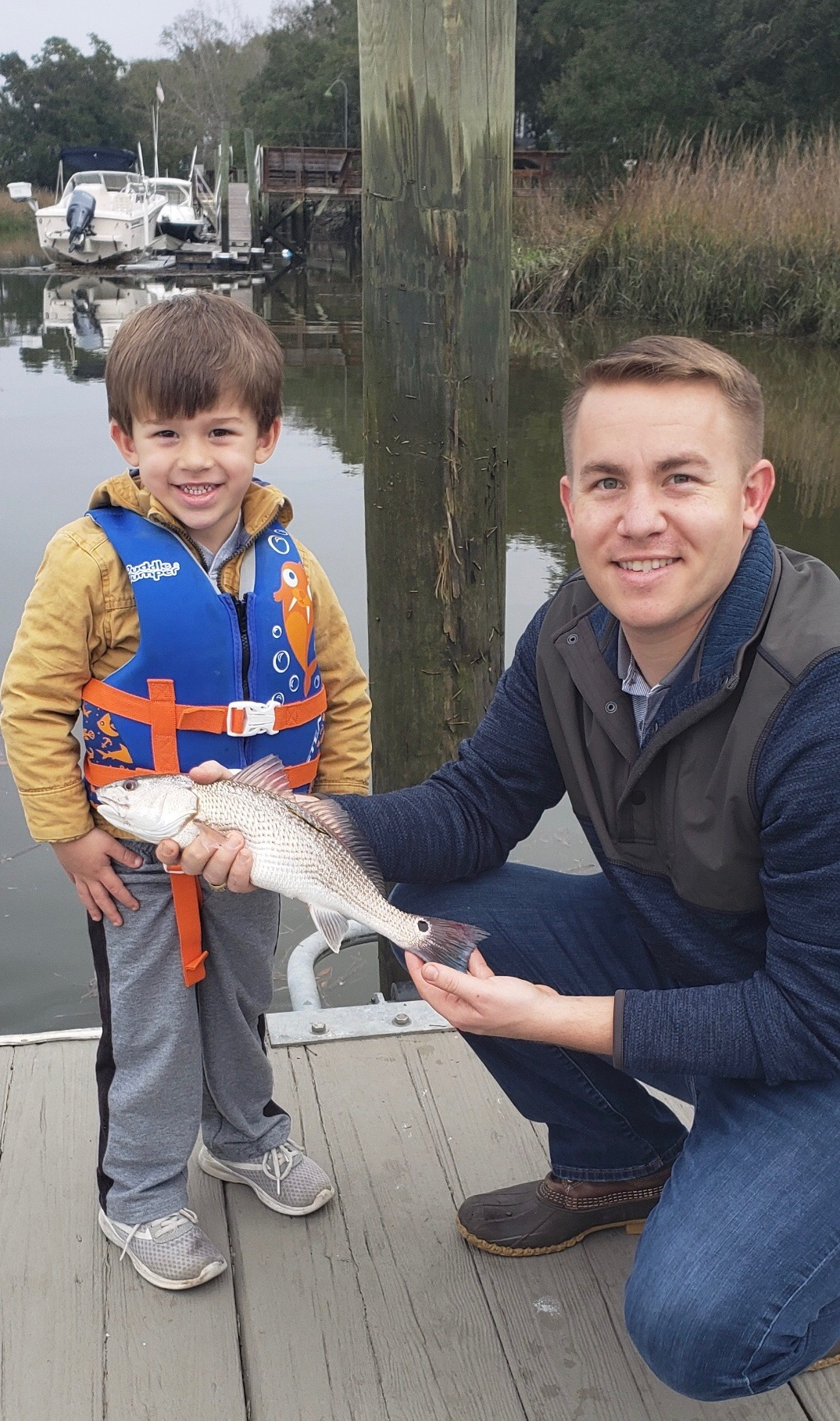 "Daniel Island resident Dianne Kirkpatrick's grandson, Walker Kirkpatrick, 3, paid a visit to the island a couple of weeks ago and caught his first fish off the Kirkpatrick's dock on Beresford Creek! Walker, pictured here with his father, Richard, hooked a 16"" redfish! According to Dianne, ""it was a grand slam day"" as Walker's Pop, Rick Kirkpatrick, caught a 17"" trout and a 17"" flounder!"