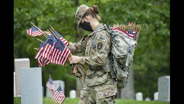 """A soldier assigned to the 3rd U.S. Infantry Regiment, known as """"The Old Guard,"""" places flags at headstones as part of Flags-In at Arlington National Cemetery, Va., May 21, 2020. For more than 50 years, soldiers assigned to the unit have honored the nation's fallen military heroes by placing U.S. flags at grave sites of every service member buried at Arlington National Cemetery and the U.S. Soldiers' and Airmen's Home National Cemetery in Washington, D.C., just before Memorial Day weekend. Elizabeth Fraser"""