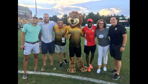 Representatives from the local nonprofit Darkness to Light pose on the field at MUSC Health Stadium with Leo the Lion and Battery legend John Wilson following the Blackbaud Crossbar Challenge at a match in 2017.