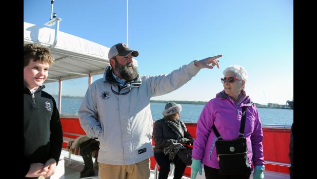 Daniel Island Ferry co-partner Scott Connelly (center) points out some sights along the journey to passengers William Hollifield (left) and Anita Koszyk (right).