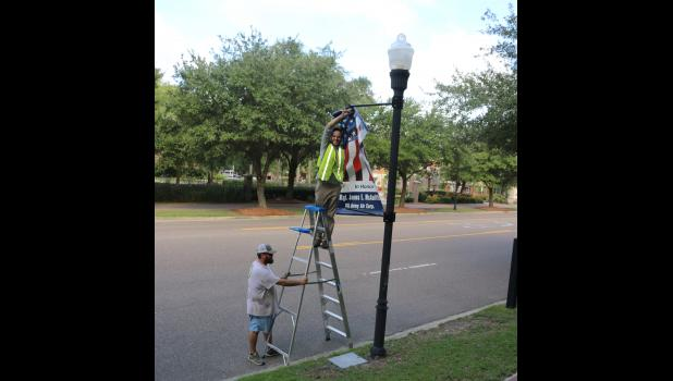 George and Mize McIngvale of McIngvale Landscape remove street flags as part of the POA preparation for Hurricane Dorian.
