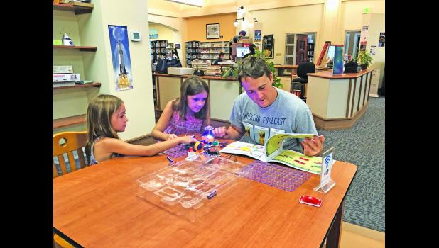 A father and his two daughters work on a STEM-based kit at the Daniel Island Library last week.