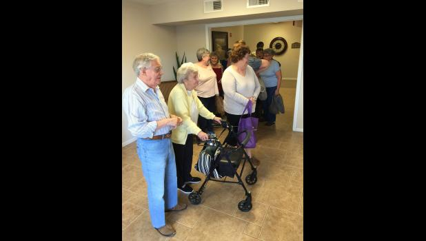 Residents at Daniel Island's Seven Farms Village, an affordable housing property for seniors that is owned by the Humanities Foundation, line up twice a month for a free food distribution sponsored by the foundation.