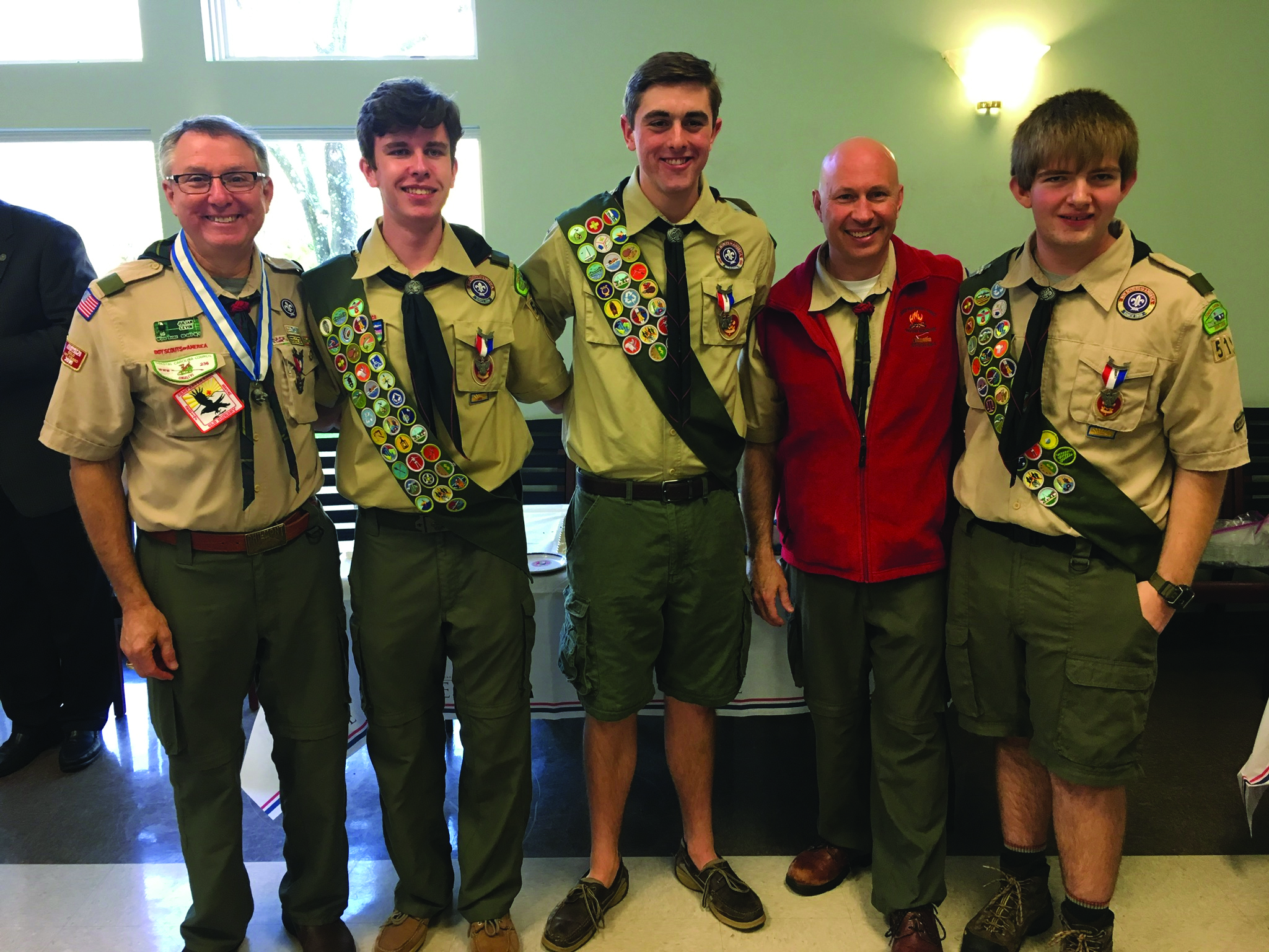 Three members of Daniel Island-based Boy Scout Troop 519 received scouting's highest honor last Sunday, March 4. Earning the prestigious Eagle Scout Award are Edward Snyder, Cameron Kimner and Cameron Bush. Each had to complete at least 21 Eagle-required merit badges, hold leadership positions in the troop, perform hours of community service, and complete an Eagle Scout Service Project. Pictured at Church of the Holy Cross after the ceremony are (left to right): Troop Committee Chair Dr. Julian Levin, Edward Snyder, Cameron Bush, Scoutmaster Tony Duttera, and Cameron Kimner.